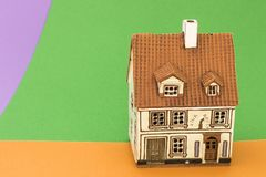 Little toy house on orange green and bright violet backgrounds. Little toy house on orange green and violet backgrounds royalty free stock photos