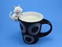 A little toy kitten hung in a cup, ready to attack the milk. Blue background. royalty free stock images