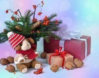 Little toy puppy, christmas tree branches, nuts and some gifts Royalty Free Stock Photos