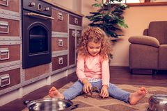 Attentive blonde girl looking downwards at her toys stock images