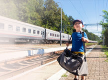 Little traveler with big bag near the train Royalty Free Stock Images