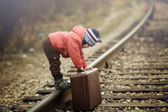 Little traveler with a old suitcase Stock Images