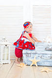 A little traveler sits on suitcases in a red dress. Stock Photos