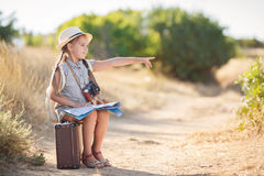 Little traveler studies the map while sitting on the old suitcase Royalty Free Stock Images