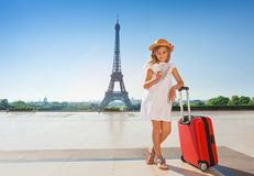 Little traveler with suitcase reading map in Paris. Portrait of elegant preteen girl standing with suitcase against the Eiffel Tower and reading a guide Map from Stock Photo