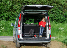 Little traveller in the car luggage. Little traveller staying in the car luggage. Family travel Stock Photo