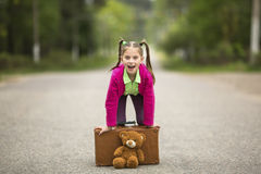 Little traveller girl on the road with a suitcase and a Teddy bear. Happy. Royalty Free Stock Photos