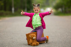 Little traveller on the road with a suitcase and a Teddy bear. Happy. Stock Photography