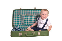 Little traveller sitting in green suitcase Stock Photo