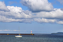 Little Traverse Bay, Petoskey Michigan. A sailboat is anchored near a water breakwall and red and white lighthouse, under bold clouds and a blue sky, on Little stock photos
