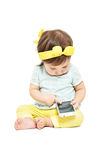 Little trendy girl, sitting touching the smartphone screen. Isolated on white background Royalty Free Stock Photography