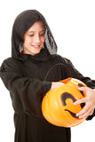 Little Trick or Treater. Little boy in his Halloween costume, picking candy from his pumpkin bucket. Isolated on white stock photos