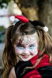 Little Trick or Treater. Little girl dressed as Harley Quinn with sugar skull make up heading out to Trick or Treat Royalty Free Stock Images