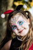 Little Trick or Treater. Little girl dressed as Harley Quinn with sugar skull make up heading out to Trick or Treat Royalty Free Stock Photography