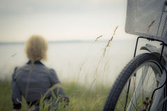 Little Trip. Young woman on the ocean bank watching at the ocean with focus on the part of nice white bicycle Royalty Free Stock Photography