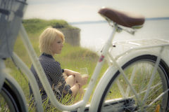 Little Trip. Young woman on the ocean bank drinking the wine with focus on the white bicycle on the foreground Royalty Free Stock Images