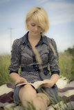Little Trip. Young woman on the ocean bank reading a book Royalty Free Stock Photos