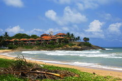 Little tropic village near ocean beach on sunny day. Long ocean wave line from white wave on yellow tropic ocean beach Stock Photo