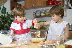 Little Twin Brothers Making a Cream For Homemade Cake in Glass Bowl Royalty Free Stock Image