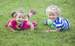 Little twins brother and sister. On a grass royalty free stock photography