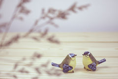 A little two ceramic birds on wooden table Royalty Free Stock Photography