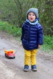 Little two year old boy carries a truck on a rope and screams or grumbles. royalty free stock photo