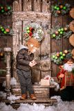 Little two year old boy dressed in braun leather jacket, pants and boots with pilot hat on posing in christmas decorations Stock Photography