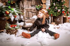 Little two year old boy dressed in braun leather jacket, pants and boots with pilot hat on posing plays with snow in christmas woo Royalty Free Stock Images