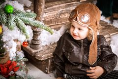 Little two year old boy dressed in braun leather jacket, pants and boots with pilot hat on posing plays with snow in christmas woo Stock Image