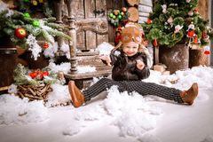 Little two year old boy dressed in braun leather jacket, pants and boots with pilot hat on posing plays with snow in christmas woo Stock Photo