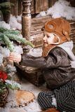 Little two year old boy dressed in braun leather jacket, pants and boots with pilot hat on posing plays with snow in christmas woo Stock Images