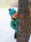 A little boy happily smiles peeking from behind a tree trunk on a winter day stock image