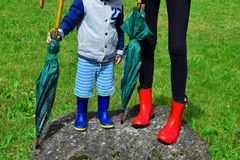 Two children wearing colorful rubber boots stock photo