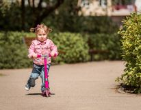 Little Two years old girl riding her scooter Royalty Free Stock Images