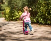Little Two years old girl riding her scooter Stock Photo