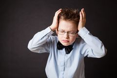 Little unhappy boy holding his head Royalty Free Stock Image