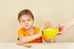 Little unhappy boy refuses to eat porridge Royalty Free Stock Photography