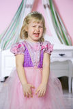 Little unhappy princess girl in pink dress and crown in her royal room is crying. Stock Images