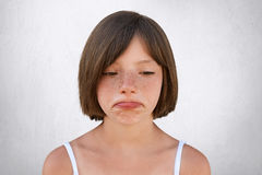 Little upset girl with freckled skin and bobbed hair, curving her lips with sorrorful expression being unhappy to find out that pa. Rents didn`t buy her toy royalty free stock images