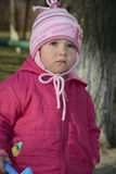 Little upset girl standing alone on a street in the spring. Royalty Free Stock Photography