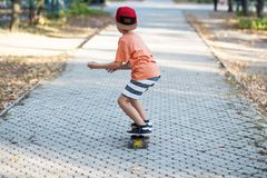Little urban boy with a penny skateboard. Kid skating in a summe Royalty Free Stock Photos
