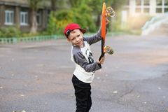 Little urban boy with a penny skateboard. Young kid riding in th Royalty Free Stock Photography