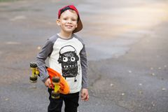 Little urban boy with a penny skateboard. Young kid riding in th Royalty Free Stock Image