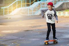 Little urban boy with a penny skateboard. Young kid riding in th Stock Photo