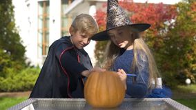 Little vampire and witch drawing scary face on pumpkin, preparing jack-o-lantern. Stock photo royalty free stock photos