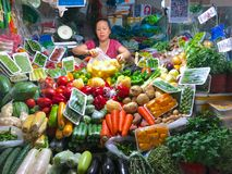 Little vegetables stand shop with woman owner of the shop. stock image