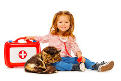 Little veterinarian with medicine box treating cat. Little girl playing veterinarian with medicine box treating cat, isolated on white royalty free stock photos