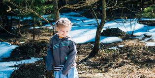 Little village girl standing in the spring forest and smiling.  royalty free stock photos