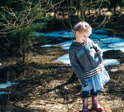 Little village girl standing in the spring forest and smiling.  stock images