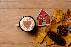 House with and coffee cup maple leaves. Little vintage house with and coffee cup maple leaves on wooden table. Above view stock photography